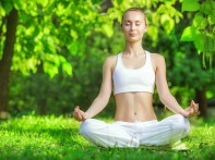 Yoga outdoors. Woman meditating in lotus position zen gesturing. Concept of healthy lifestyle and relaxation